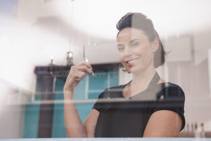Glimlachende het haarschaar van de kapperholding stock foto
