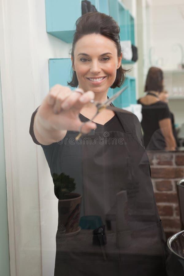 Glimlachende het haarschaar van de kapperholding stock fotografie
