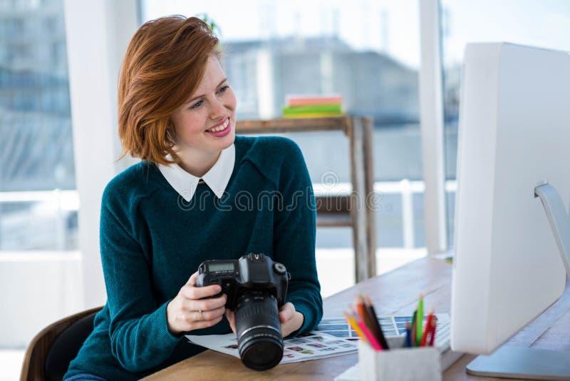 glimlachende hipster fotograaf die beelden op haar camera bekijken royalty-vrije stock afbeeldingen