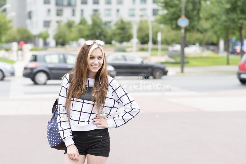 Glimlachende hipster jonge vrouw met rugzak in straat het kijken royalty-vrije stock afbeeldingen