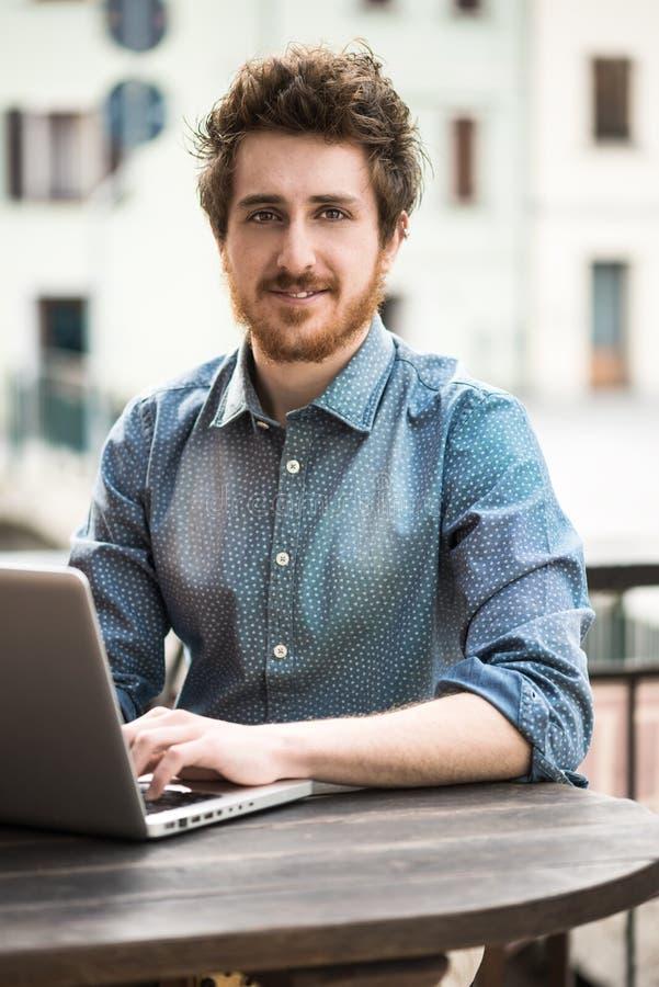 Glimlachende hipster mens die laptop in openlucht met behulp van royalty-vrije stock fotografie