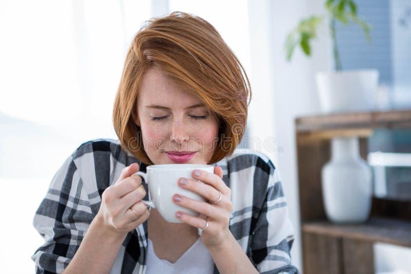 glimlachende hipster vrouw die een kop van koffie ruiken stock foto's