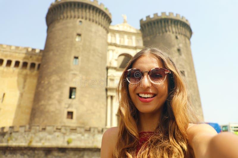 Glimlachende hipster vrouw met zonnebril die selfie foto in Napels met Castel Nuovo-kasteel op de achtergrond nemen, Napels, Ital stock foto