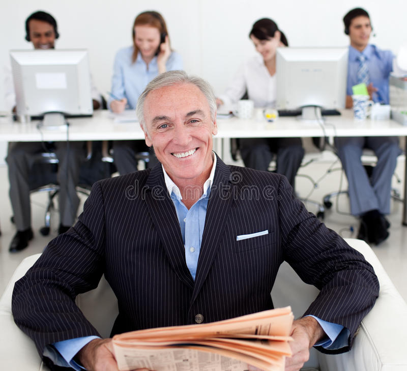Glimlachende hogere manager die een krant leest stock afbeelding