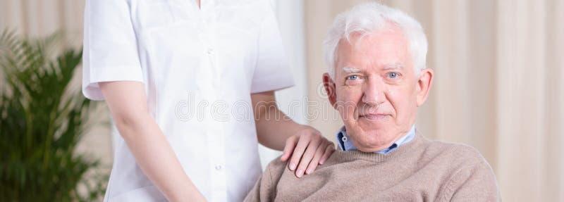 Glimlachende hogere mens en verpleegster stock afbeelding