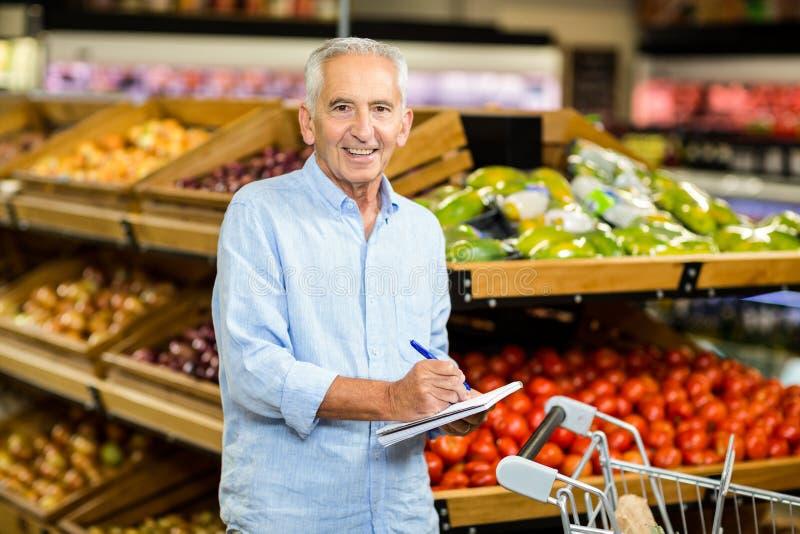 Glimlachende hogere mens met het winkelen lijst stock fotografie