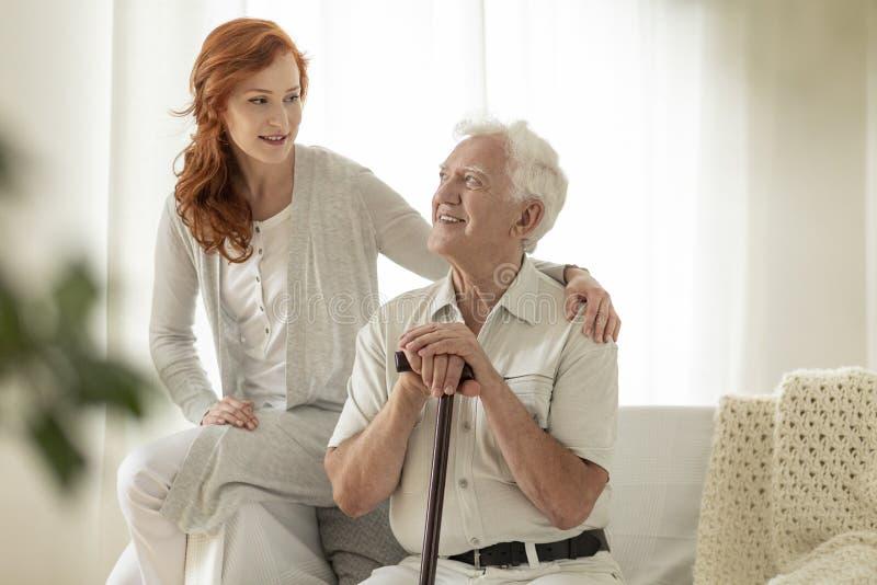 Glimlachende hogere mens met wandelstok en zijn gelukkige granddaughte royalty-vrije stock foto's