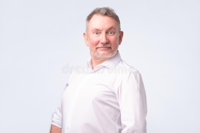 Glimlachende hogere mens in wit overhemd die en zich bij camera bevinden glimlachen die goed voelen royalty-vrije stock fotografie