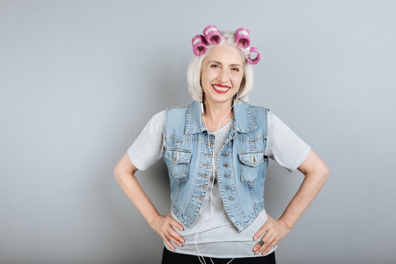 Glimlachende hogere prettige vrouw die hoofdtelefoons met behulp van royalty-vrije stock foto's