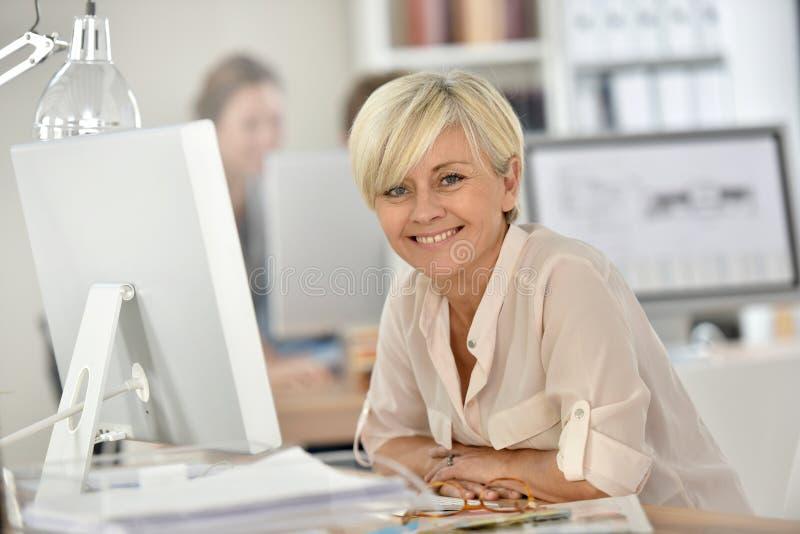 Glimlachende hogere vrouw die aan Desktop op kantoor werken stock afbeeldingen