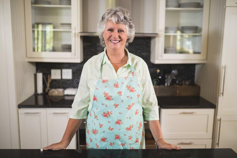 Glimlachende hogere vrouw die in keuken zich thuis bevinden stock afbeelding