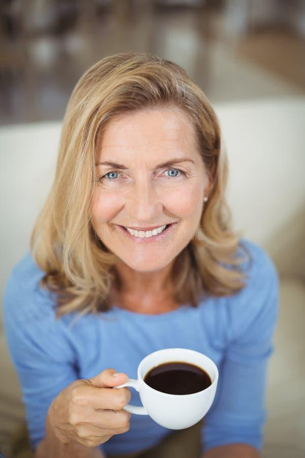 Glimlachende hogere vrouw die kop van koffie in woonkamer hebben royalty-vrije stock foto