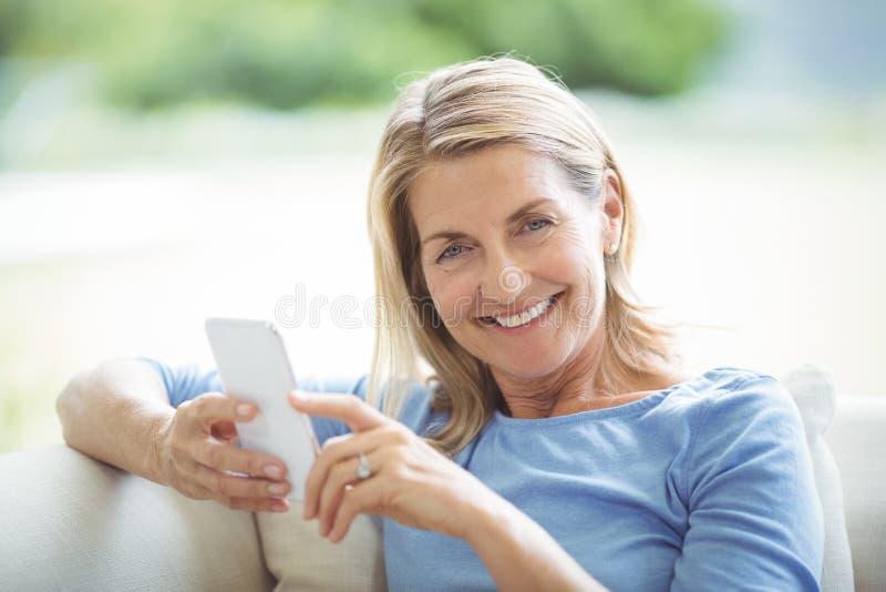 Glimlachende hogere vrouw die mobiele telefoon in woonkamer met behulp van royalty-vrije stock foto
