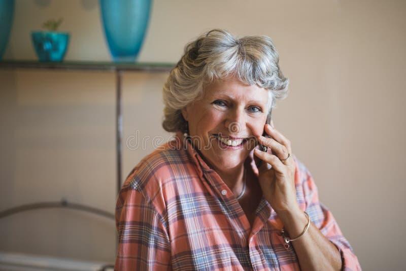 Glimlachende hogere vrouw die op telefoon thuis spreken royalty-vrije stock foto's