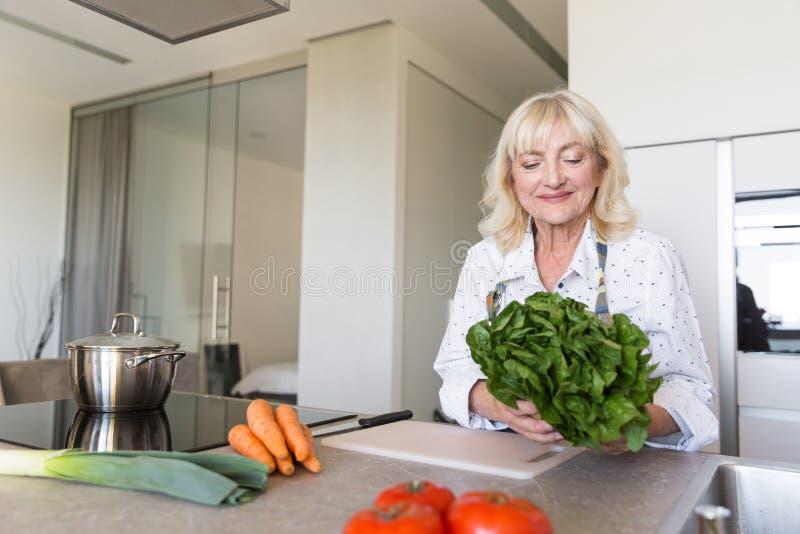 Glimlachende hogere vrouw die salade voorbereiden bij de keuken royalty-vrije stock afbeelding