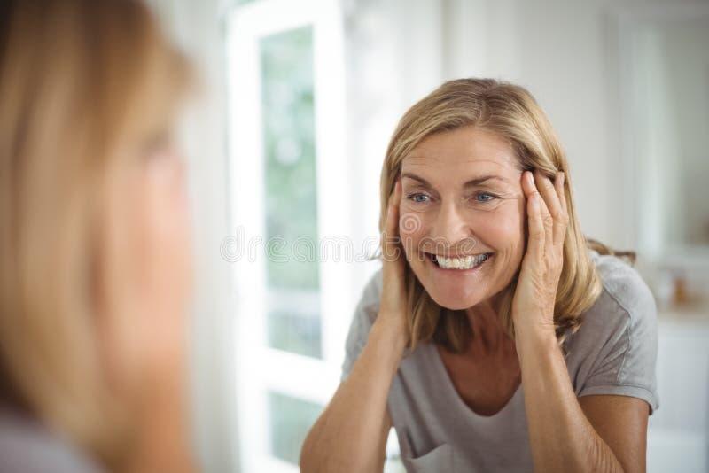 Glimlachende hogere vrouw die spiegel bekijken royalty-vrije stock foto