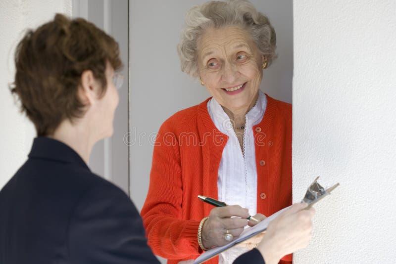 Glimlachende hogere vrouw die verzoek ondertekent
