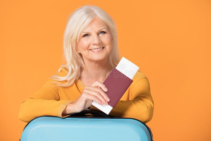 Glimlachende hogere vrouw met koffer en paspoort stock afbeelding