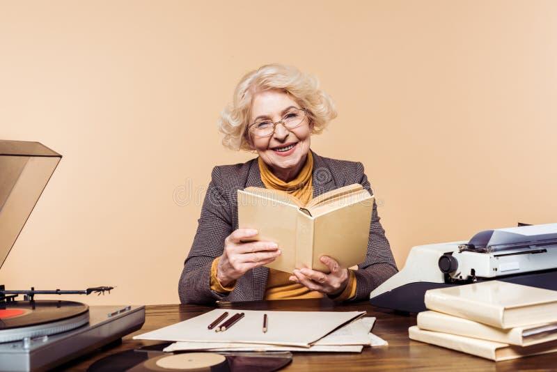 glimlachende hogere vrouw in oogglazen met boekzitting bij lijst met vinylschijfplatenspeler stock afbeelding