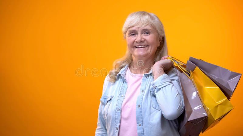 Glimlachende hogere vrouwelijke holding het winkelen zakken, prettige vrije tijd, zwarte Vrijdag stock afbeelding