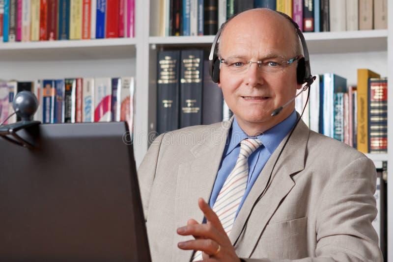 Glimlachende hoofdtelefoon tussen mens en computer stock afbeeldingen