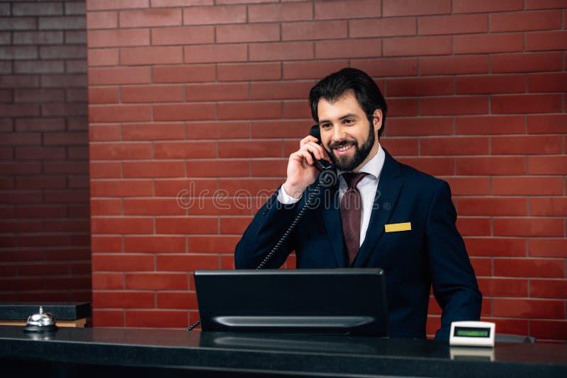 glimlachende hotelreceptionnist die telefoongesprek nemen stock afbeelding