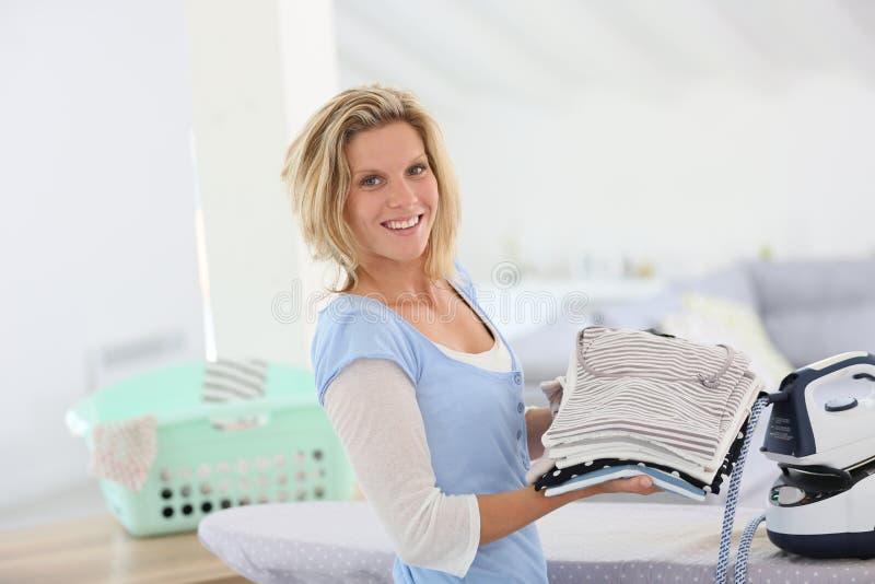 Glimlachende huishoudster het strijken kleren stock afbeeldingen