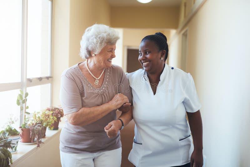 Glimlachende huisverzorger en hogere vrouw die samen lopen stock afbeelding