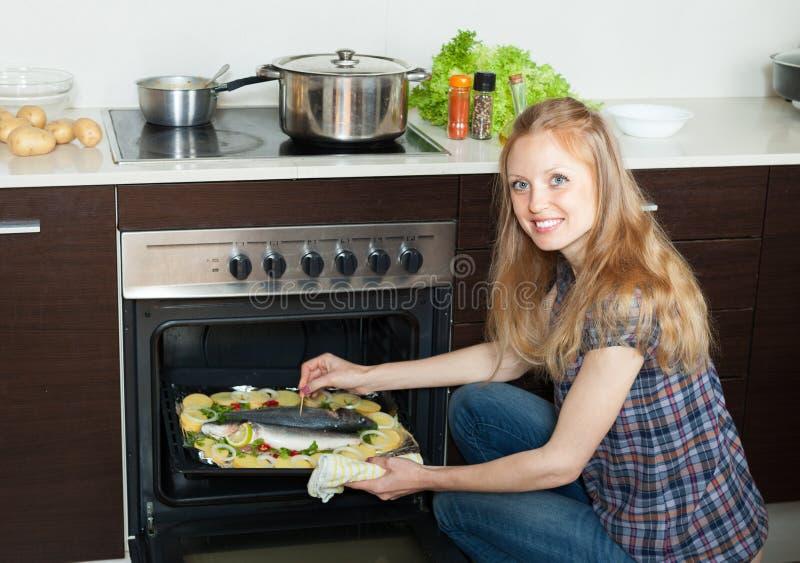 Glimlachende huisvrouw het koken zeevissen en aardappels op blad p royalty-vrije stock fotografie
