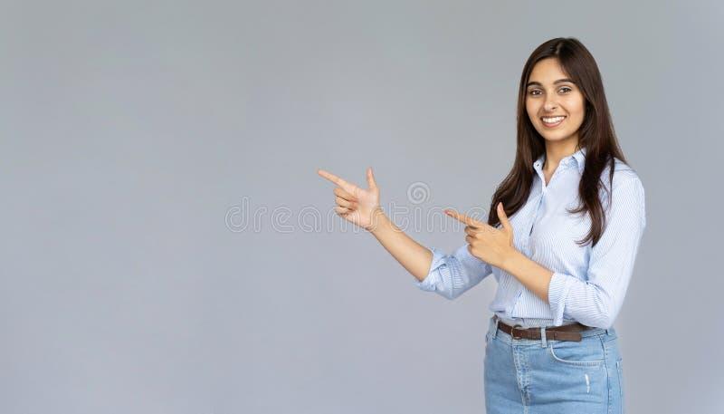 Glimlachende Indische vrouw die op exemplaarruimte richten die op grijze studioachtergrond wordt geïsoleerd royalty-vrije stock foto