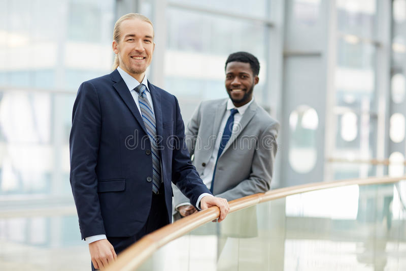 Glimlachende Internationale Partners in de Bureaubouw stock afbeeldingen