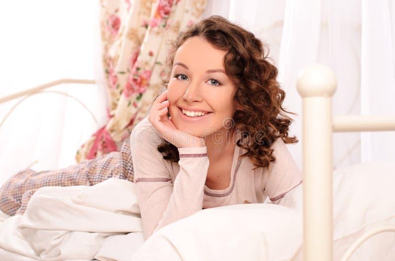 Glimlachende jonge aantrekkelijke vrouw die op bed liggen royalty-vrije stock afbeelding