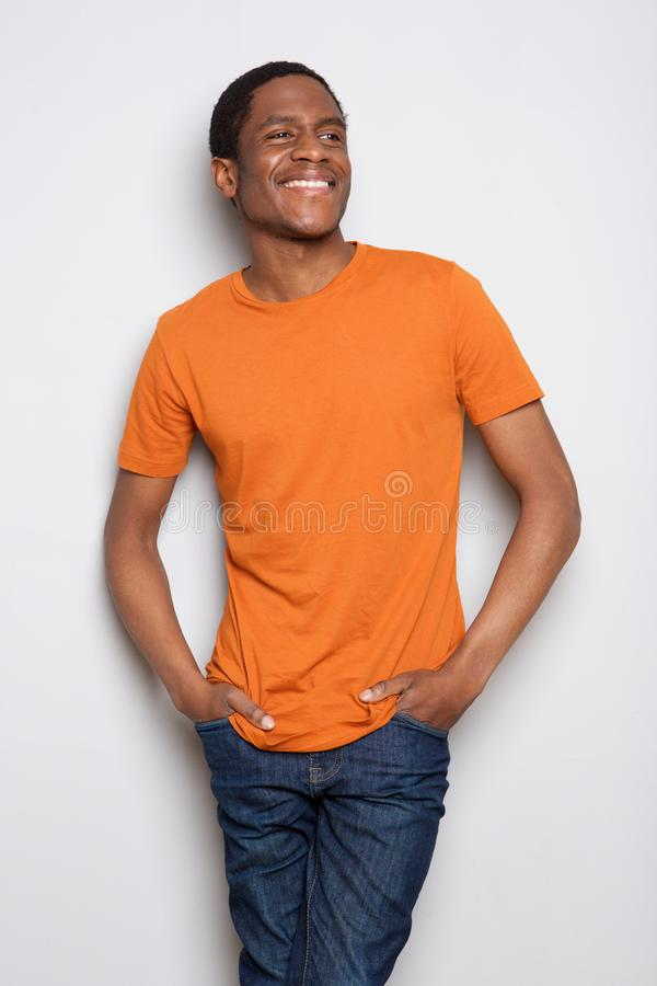 Glimlachende jonge Afrikaanse Amerikaanse mens die zich tegen witte achtergrond bevinden royalty-vrije stock afbeelding