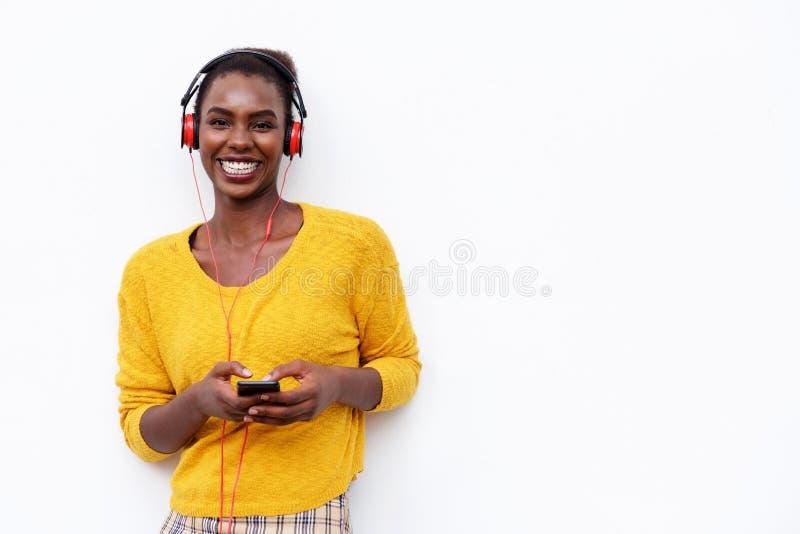 Glimlachende jonge Afrikaanse Amerikaanse vrouw die aan muziek met hoofdtelefoons en mobiele telefoon tegen geïsoleerde witte ach stock foto's