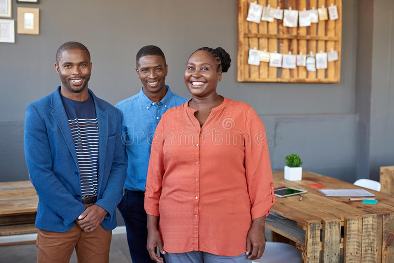 Glimlachende jonge Afrikaanse medewerkers die zich in een bureau verenigen royalty-vrije stock afbeeldingen