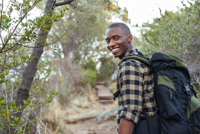 Glimlachende jonge Afrikaanse mens die in de heuvels wandelen royalty-vrije stock fotografie
