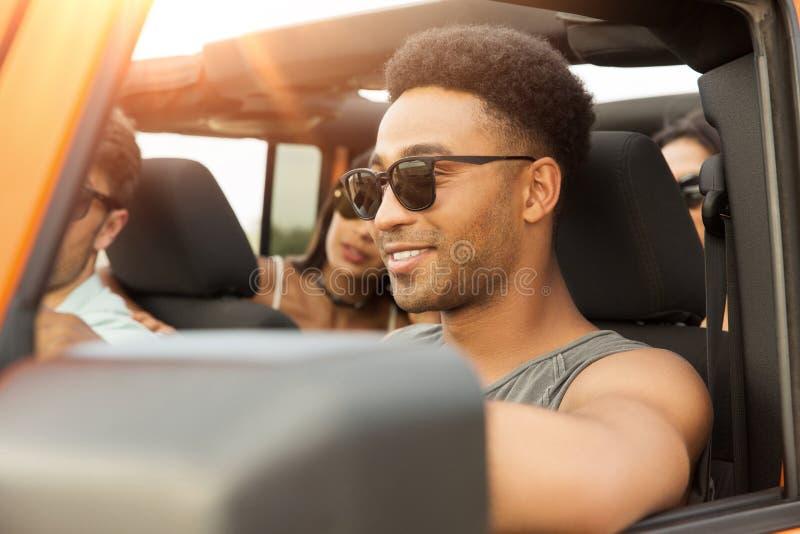 Glimlachende jonge Afrikaanse mens die een auto drijven stock foto
