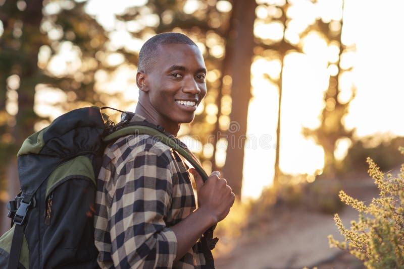 Glimlachende jonge Afrikaanse mens die langs een sleep bij schemer wandelen stock foto's