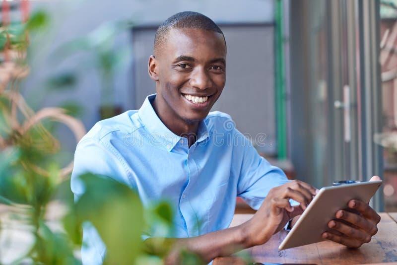 Glimlachende jonge Afrikaanse mens die online bij een stoepkoffie werken stock foto's