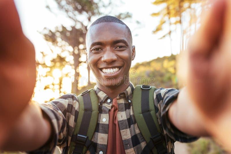 Glimlachende jonge Afrikaanse mens die selfies terwijl in openlucht wandeling alleen nemen stock afbeeldingen