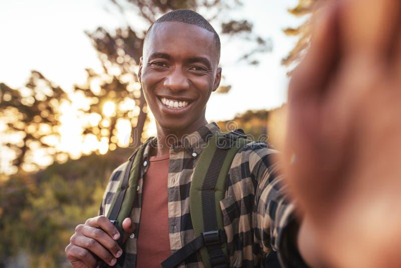 Glimlachende jonge Afrikaanse mens die selfies terwijl uit wandeling nemen royalty-vrije stock afbeeldingen