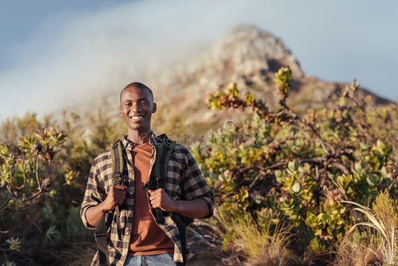 Glimlachende jonge Afrikaanse mens die van trek in de bergen genieten royalty-vrije stock foto