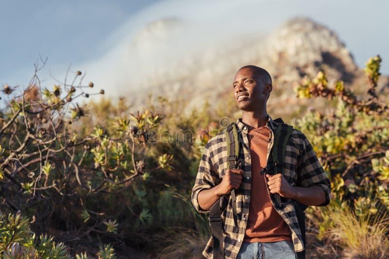 Glimlachende jonge Afrikaanse mens uit voor een bergstijging stock foto