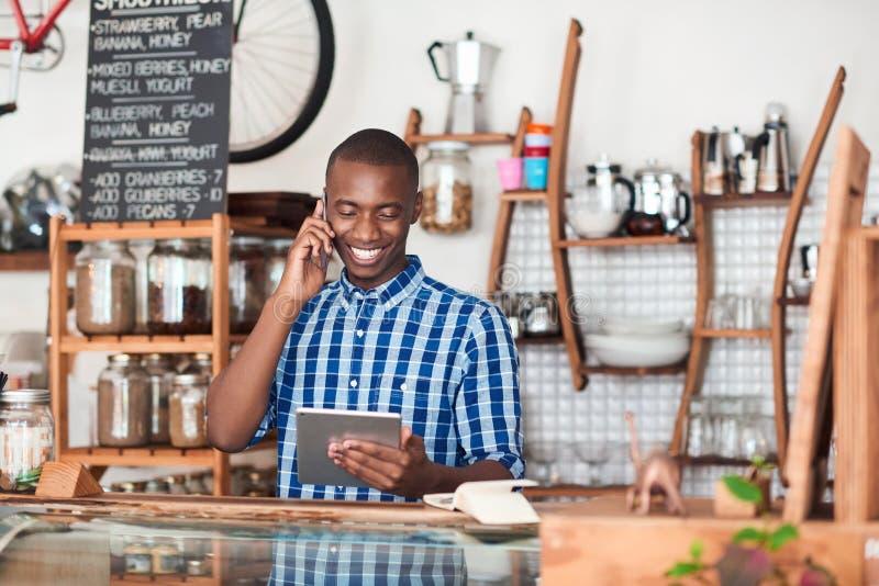 Glimlachende jonge Afrikaanse ondernemer bezig het werken in zijn koffie royalty-vrije stock foto's