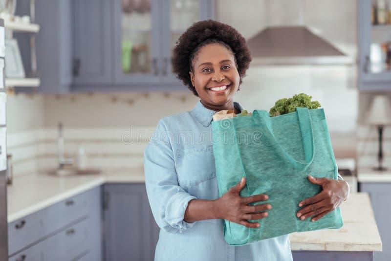 Glimlachende jonge Afrikaanse vrouw die zich in haar keuken met kruidenierswinkels bevinden stock foto