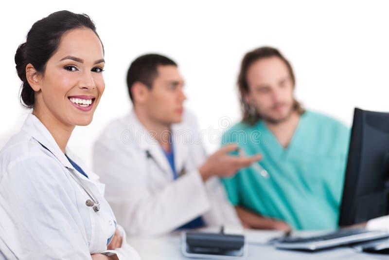 Glimlachende jonge arts met andere artsen achter haar stock foto
