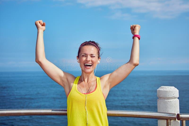 Glimlachende jonge atleet die zich bij dijk verheugen royalty-vrije stock afbeeldingen