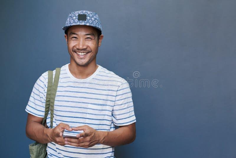 Glimlachende jonge Aziatische mens die een cellphone buiten gebruiken stock foto's