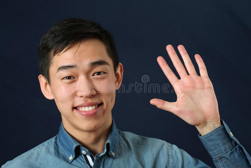 Glimlachende jonge Aziatische mens die zijn palm golven royalty-vrije stock foto