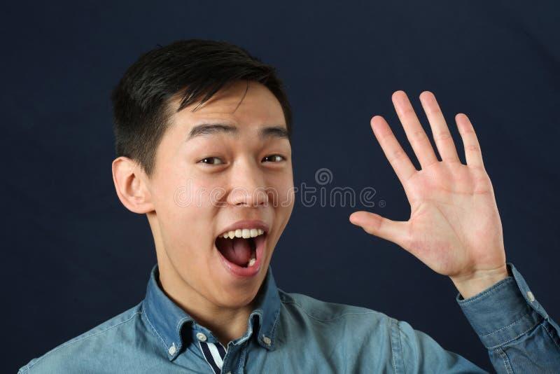 Glimlachende jonge Aziatische mens die zijn palm golven en camera bekijken stock foto's